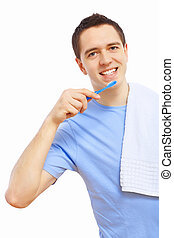 Young man at home brushing teeth