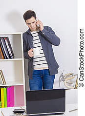 young man at home or the office with the cup of coffee and the mobile phone