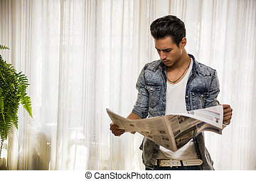 Young man at home reading newspaper