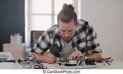 Young man at repair cafe repairing household electrical devices.