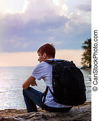Young Man at Seaside - Young Man with Backpack sit on the...