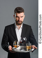 Young man at tasting session. Three different types of drink on a metal tray
