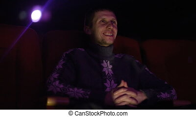 Young man at the cinema watching a movie - Young man sitting...