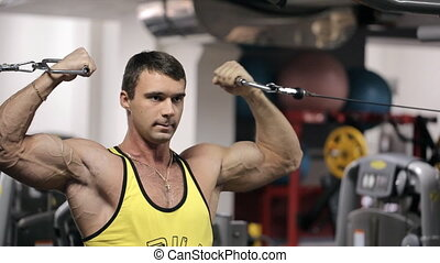 Young man at the gym trains his huge arm muscles