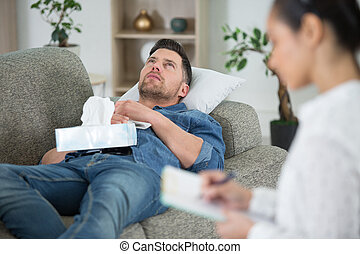 young man at the psychotherapist lying on couch emotionally speaking