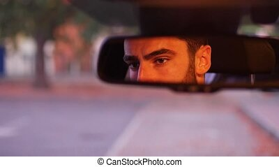 Young man at wheel of his car looking in mirror