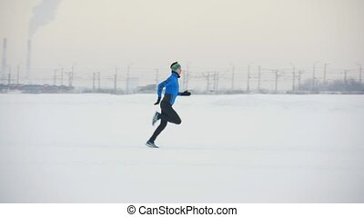 Young man athlete running in winter outdoor