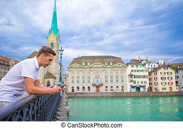 Young man background famous Fraumunster Church and river Limmat, Switzerland.