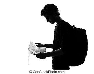 young man backpacker traveler looking at map silhouette in studio isolated on white background