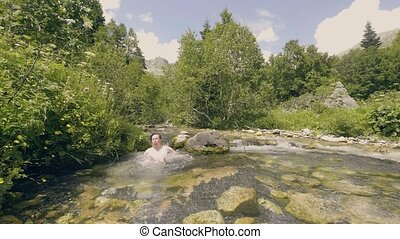 Young man bathing in refreshing water of stony river slow...