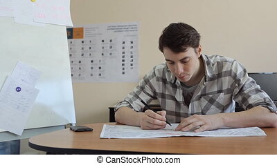 Young man bent over plan on table and draws on it with a pen sitting.