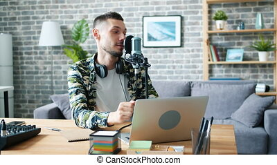Young bearded man blogger is recording audio for global broadcasting at home using mic and laptop talking smiling. Blogging and modern technology concept.
