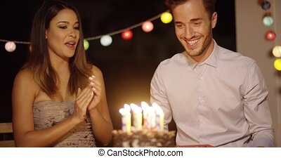 Young man blowing out his birthday cake - Young man blowing...