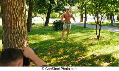 Young man body-builder posing to photographer in the park