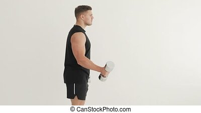 Fitness, training, workout, bodycare and wellness concept. Young man bodybuilder is lifting dumbbells at home practicing biceps exercise on white background, side view. Hard strength workout.