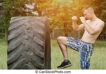Young man boxing with the tire. Workout