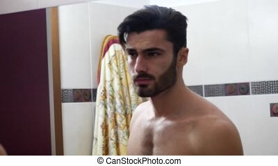 Young Man Brushing and Combing Hair in Mirror - Shirtless...