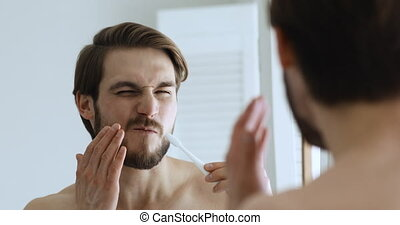 Young man holding toothbrush brushing teeth feeling sudden pain in sensitive bleeding gums looking in bathroom mirror. Oral cavity problems, caries and tooth ache, gingivitis. Toothache concept.