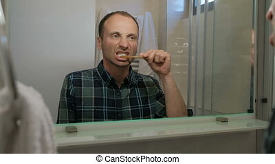 Young man brushing teeth while standing in bathroom indoors.