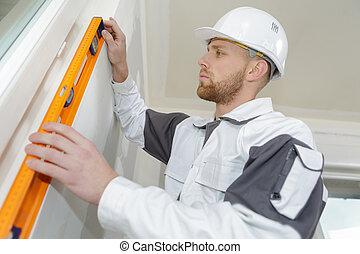 young man builder in building helmet holding spirit level