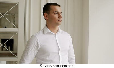 young man businessman in a white shirt stands at the window