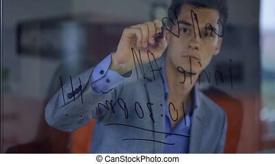 Young man businessman writes with marker on transparent glass, giving lessons to their colleagues in reflectivity.
