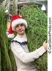 Young man buying a Christmas tree in the store