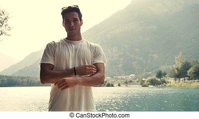 Young man by lake looking at camera and smiling