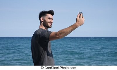 Young man by the sea taking selfie photo - Athletic man at...