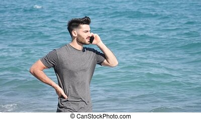 Young man by the sea talking on mobile phone