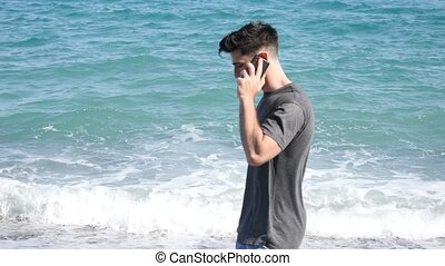 Young man by the sea talking on mobile phone - Athletic man...
