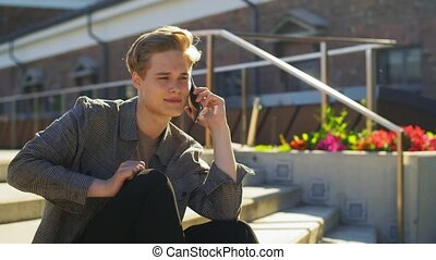 young man calling on smartphone on roof top - technology, ...