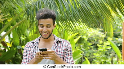 Young Man Calling Using Cell Smart Phone Smiling Outdoors...