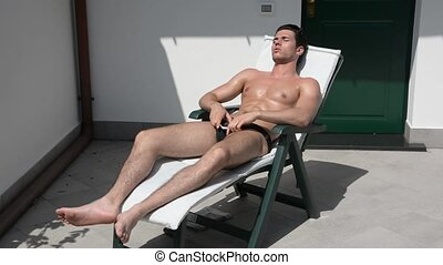 Young Man Calling with Cell Phone on Lounge Chair -...