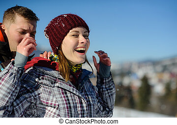 Young man carefully shakes snow from clothes of girlfriend.