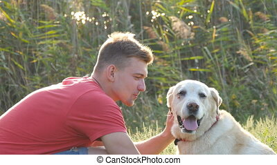 Young man caress, hugging and kissing his labrador outdoor at nature. Playing with golden retriever. Dog licking male face. Love and friendship with domestic animal. Landscape at background. Close up