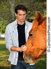Young man caressing a horse