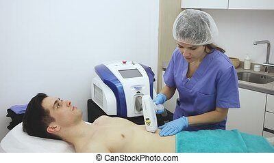 Young man caring of his skin getting laser hair removal in ...