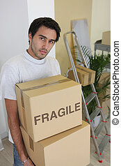 Young man carrying cardboard boxes on moving day