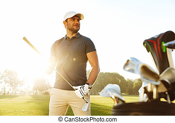 Young man carrying golf club while standing on field