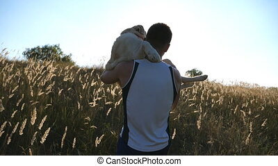 Young man carrying on hands his dog by field. Playing with...