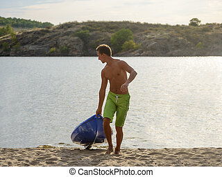 Young Man Carrying out Kayak to the Sand Beach from the Water on Beautiful River or Lake at the Evening