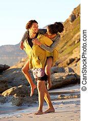 Young man carrying woman on his back at the beach