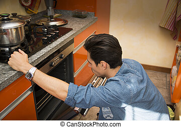 Young man checking food he baked in oven