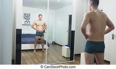 Young man checking his muscles in front of a mirror in the bedroom