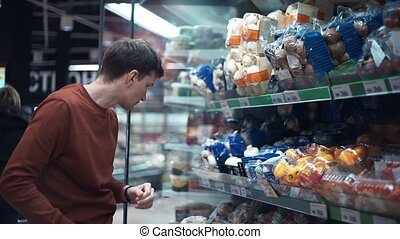 Young man chooses mushrooms on shelves full of food at supermarket