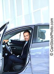 Young man choosing car at salon