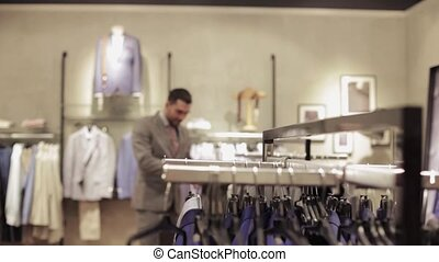 young man choosing clothes in clothing store