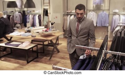 young man choosing clothes in clothing store - sale,...