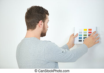 young man choosing color for walls to paint
